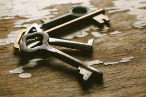 Four keys on old crack background, close up